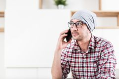 Бизнесмен хипстера сидя на его офисе и вызывая на мобильном телефоне ?? стоковые фото