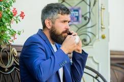 Бизнесмен человека бородатый сидит терраса с smartphone и чашкой кофе Позаботьтесь о дело даже пока насладитесь кофе стоковая фотография