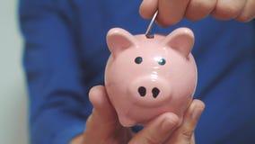Бизнесмен человек делает сбережения кладет монетки в копилку E видео замедленного движения сбережениа дег банка piggy кладя сток-видео
