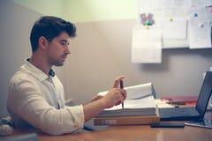 Бизнесмен читая контракт и сидя в офисе Стоковые Фотографии RF