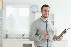 Бизнесмен читая новости пока имеющ завтрак Стоковое фото RF