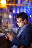 Бизнесмен читая таблетку в коктейль-баре Стоковые Фото