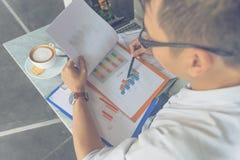 Бизнесмен читая финансовый номер на отчете стоковое изображение rf