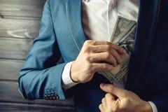 Бизнесмен, член или офицер кладут взятку в его карманн Стоковое Изображение RF