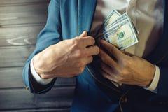 Бизнесмен, член или офицер кладут взятку в его карманн Стоковое Изображение