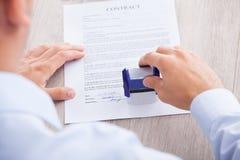 Бизнесмен штемпелюя бумагу контракта на таблице Стоковое фото RF