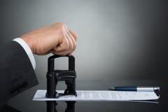 Бизнесмен штемпелюя документ контракта на столе офиса стоковые фото