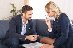 Бизнесмен flirting с молодой коммерсанткой в офисе Стоковые Изображения