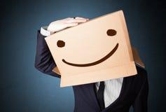 Бизнесмен gesturing с картонной коробкой на его головке с smil Стоковые Фотографии RF