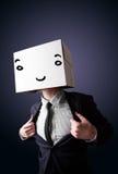 Бизнесмен gesturing с картонной коробкой на его головке с smil Стоковые Изображения