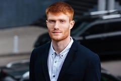 Бизнесмен Redhead смотря камеру outdoors Стоковые Изображения