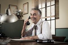 бизнесмен 1950s усмехаясь на телефоне Стоковые Изображения RF