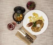 Бизнес-ланч: Маленькая шницель сосиски с кипеть картошками и кетчуп Послуженный на белой плите фарфора с вилкой и ножом o Стоковые Фото