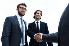 Бизнес-группа приветствует партнера с рукопожатием Стоковые Изображения
