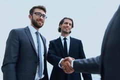 Бизнес-группа приветствует партнера с рукопожатием Стоковые Фото