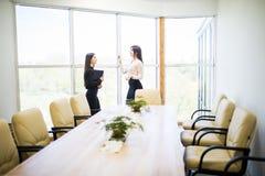 Бизнес-леди дает инструкции работы к женщине subordonates в современном офисе Стоковое Изображение RF