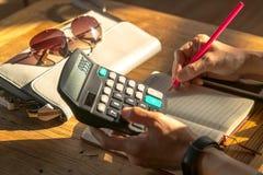 Бизнес-леди высчитывают расход на деревянном столе Стоковое фото RF