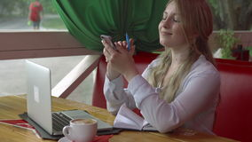 Бизнес-леди в кафе работая с компьтер-книжкой и тетрадью smartphone акции видеоматериалы