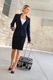 Бизнес-леди в командировке идя с сумкой колеса и говорит Стоковое Изображение
