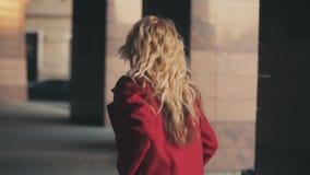 Бизнес-леди в красном пальто идет к деловому центру и смотрит на вахте, она последняя для работы или встречи акции видеоматериалы