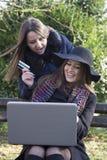 2 бизнес-леди в парке для того чтобы купить компьтер-книжку Стоковая Фотография