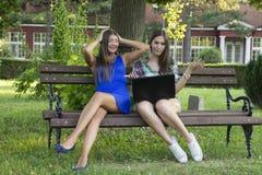 2 бизнес-леди в парке для того чтобы купить компьтер-книжку Стоковое Фото