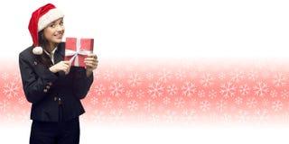 Бизнес-леди в шляпе santa держа подарок Стоковая Фотография
