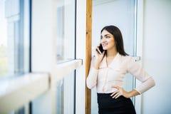 Бизнес-леди говорит на телефоне около больших окон офиса в современном офисе Стоковые Изображения RF