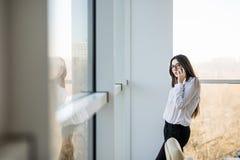 Бизнес-леди говорит на телефоне около больших окон офиса Стоковое Изображение