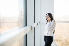 Бизнес-леди говорит на телефоне около больших окон офиса Стоковые Изображения