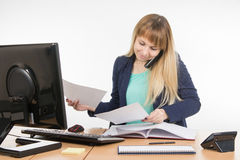 Бизнес-леди говоря на телефоне и смотря печатные документы Стоковое Фото
