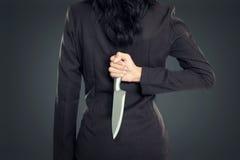 Бизнес-леди держа нож за его назад Стоковые Изображения