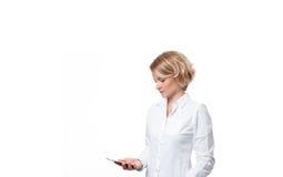 Бизнес-леди держа smartphone на белой предпосылке Стоковые Фото
