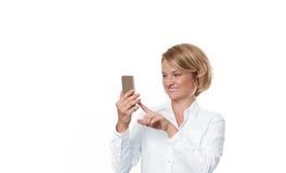Бизнес-леди держа smartphone на белой предпосылке Стоковые Изображения