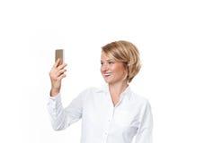 Бизнес-леди держа smartphone на белой предпосылке Стоковые Фотографии RF