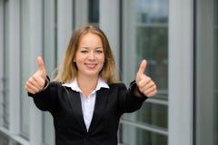 Бизнес-леди детенышей довольно белокурая показывая большие пальцы руки вверх Стоковое Изображение RF