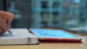 Бизнес-леди делая примечания и используя цифровую таблетку видеоматериал