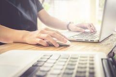 Бизнес-леди используя мышь и портативный компьютер в домашнем офисе Re Стоковое фото RF