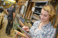 Бизнес-леди используя таблетку в складе Стоковая Фотография