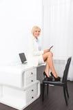 Бизнес-леди используя таблетку сидя на столе Стоковые Фото