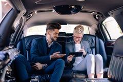 Бизнес-леди и человек имея обсуждение в лимузине Стоковые Изображения RF