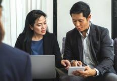 Бизнес-леди и человек используя таблетку, тетрадь к строгая работе на Стоковые Изображения