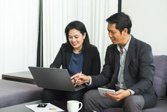 Бизнес-леди и человек используя таблетку, тетрадь к строгая работе на Стоковое Фото