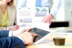 Бизнес-леди и человек работая и анализируя финансовые диаграммы на диаграммы Стоковая Фотография