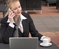 Бизнес-леди на мобильном телефоне сидя outdoors с компьтер-книжкой Стоковые Фотографии RF
