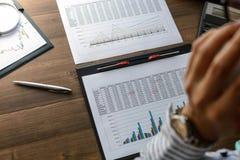 Бизнес-леди на рабочем месте на деревянной таблице офиса анализирует данные, план-графики, оценивает, делает вычисления на кальку Стоковое фото RF