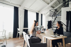 Бизнес-леди обсуждают на встрече в современном офисе 2 женских сотрудника сидя на такой же таблице с компьтер-книжками стоковая фотография