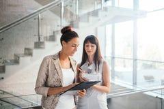 2 бизнес-леди обсуждая контрольный списоок Стоковая Фотография