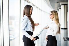 Бизнес-леди обсуждая последние новости компании в офисе Стоковые Фото