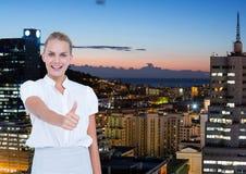 Бизнес-леди перед городом на ноче с большим пальцем руки вверх Стоковое фото RF